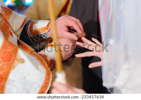 Wedding in Orthodox church. The ceremony of exchanging rings. - stock photo
