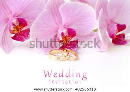 Wedding invitation: Golden Wedding rings on background of orchids - stock photo