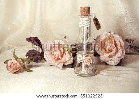 Wedding invitation in a glass bottle and pink roses