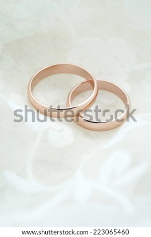 Wedding invitation with rose gold rings on white fabric