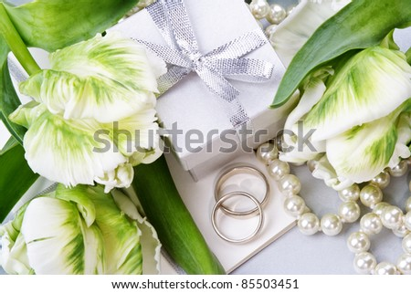 Wedding invitation with wedding rings, pearls, gift box and white tulips. Still life. - stock photo