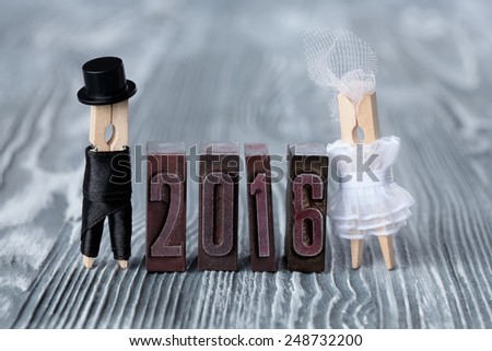 Wedding invitation. 2016 written with colored vintage letterpress. Groom in black suit and bride in white dress. Clothespins. (Soft focus) - stock photo
