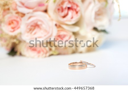 wedding items , wedding rings on a background of a bouquet of flowers . - stock photo