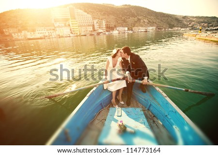Wedding kiss on the retro boat. Beautiful young couple kissing in a boat with oars. - stock photo