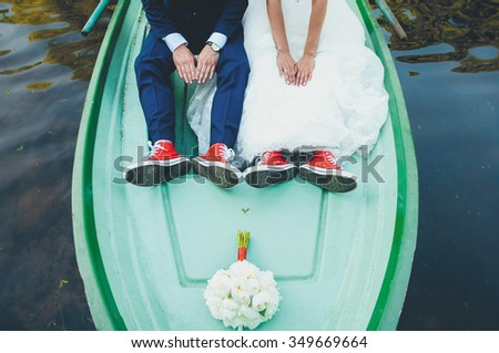 wedding legs in red gym shoes on a boat - stock photo