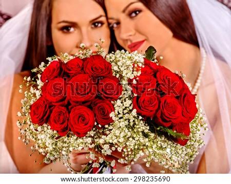 Wedding lesbians girl in bridal dress holding flower. Sharpness of rose. - stock photo