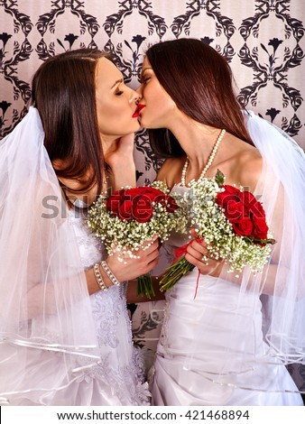 Wedding lesbians girl in bridal dress kissing. Untraditional wedding of two lesbians girls. - stock photo