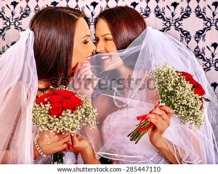 Wedding lesbians girl in bridal dress kissing. Wallpaper in background - stock photo