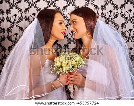 Wedding lesbians girl in bridal dress. lesbians keeps flower. Wallpaper background. - stock photo