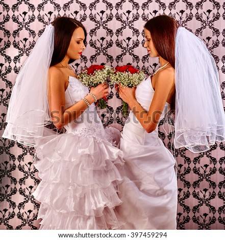 Wedding lesbians girl  in bridal dress looking at each other and keep roses bouquet. - stock photo