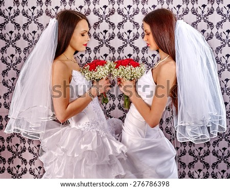 Wedding lesbians girl in bridal dress. Roses bouquet. - stock photo