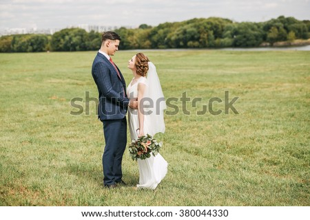 Wedding, love, spring, summer. Lovely couple standing on green meadow at sunny day