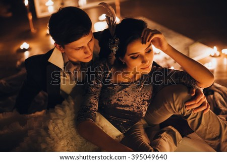 Wedding. Night. Candles. Artwork. Bride in a gray dress and groom in a suit lying on a wooden floor among candles and mirrors