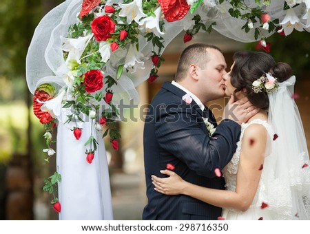 wedding of happy couple under  decorated with red roses and white lilies arch, firs kiss