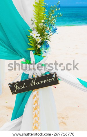 Wedding on the beach . Just married. Wedding arch decorated with flowers on tropical sand beach. - stock photo