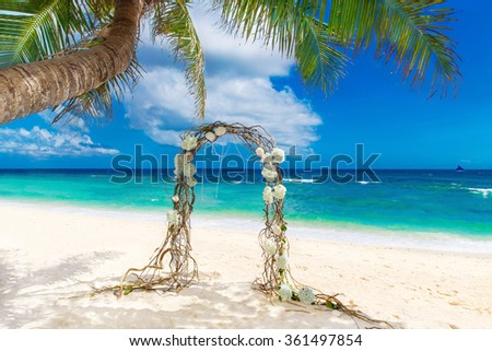 Wedding on the beach . Wedding arch decorated of vines and flowers on tropical sand beach. Wedding and honeymoon concept. - stock photo