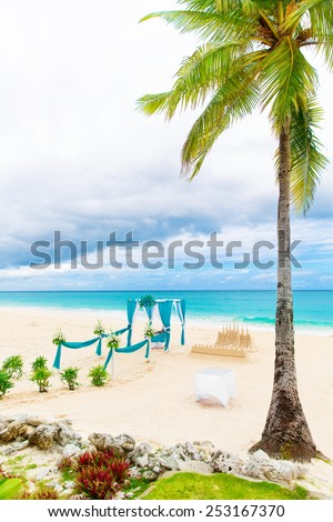 Wedding on the beach . Wedding arch decorated with flowers on tropical sand beach under the palm tree. - stock photo