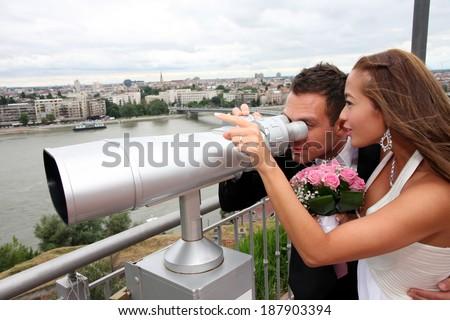 Wedding on the nature, young wedding couple with tourist binoculars - stock photo