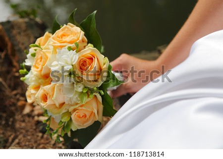 Wedding orange roses bouquet with white flowers on nature background, focused to the flowers - stock photo