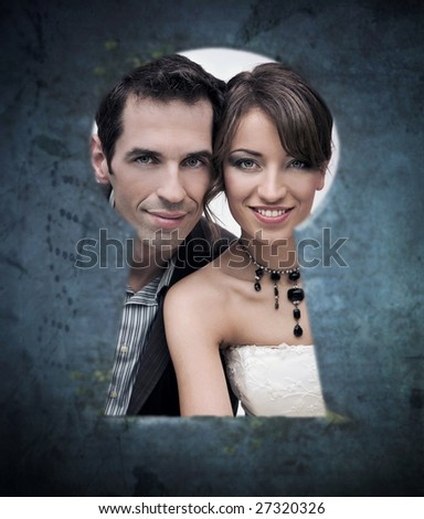 Wedding pair look out keyhole - stock photo