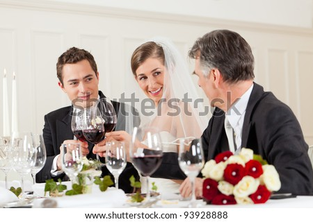 Wedding party at dinner - the bridal couple is clinking glasses with wine