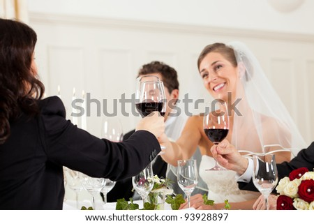 Wedding party at dinner - the bridal couple is clinking glasses with wine - stock photo