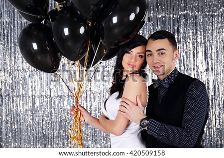 Wedding photo. Young couple with black balls on glittering background - stock photo