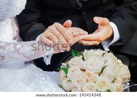Wedding photograph of a young couple of lovers who are just married, are close to each other in harmony, love and happiness. Groom holds the bride's hand in his hand.