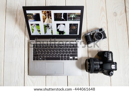 Wedding photographer works on laptop screen close-up. Top view on digital and film photo cameras lying next to laptop with wedding photos on light wooden background. - stock photo