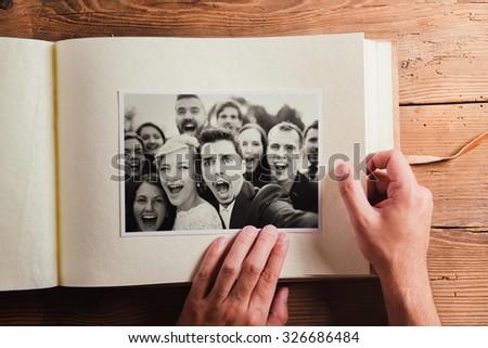 Wedding photos in album. Studio shot on wooden background. - stock photo