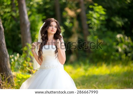 Wedding picture of happy brunette bride outside. - stock photo