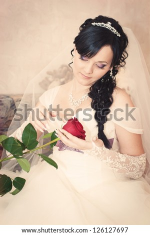 wedding portrait of beautiful smiley bride with red rose