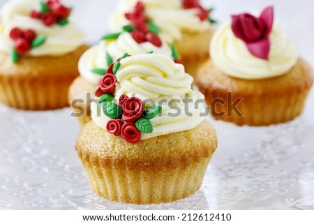 Wedding reception cupcakes decorated with sugarcraft red roses - stock photo