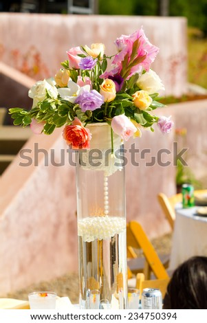 Wedding reception decor with flower center pieces on tables. - stock photo