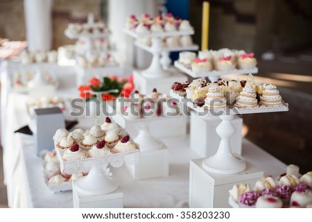 Wedding reception dessert table with delicious decorated white cupcakes with frosting closeup - stock photo