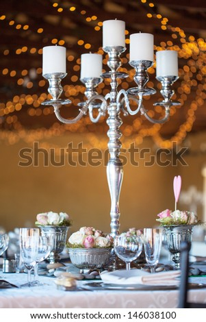 Wedding reception hall with decorated tables, selective focus with blurred fairy lights in background - stock photo