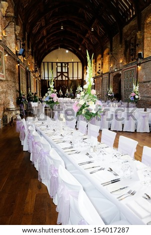 Wedding reception table decoration showing flower arrangement and silver cutlery