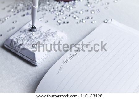Wedding register with white pen and white tablecloth - stock photo