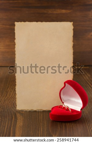 wedding ring and aged paper on wooden background - stock photo