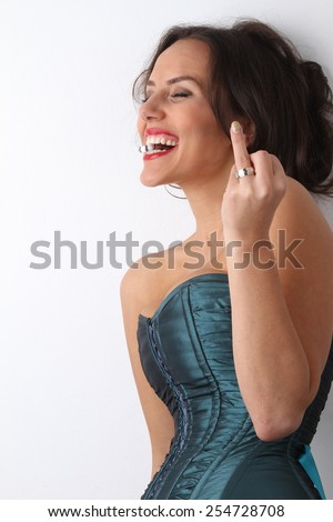 wedding ring - engagement ring - beautiful young brunette in a green blue corset with red lipstick smiles and provocative posing with a golden ring  between white teeth and a bright red lips
