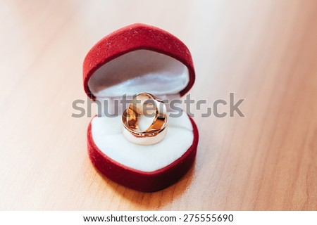 Wedding ring in red gift box on the woodden background. Wedding ring in a gift box in heart shape. Shot with a shallow depth of field - stock photo