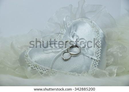 wedding ring on heart pillow, soft fabric background, wedding symbols - stock photo