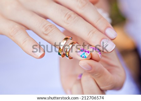 Wedding ring on the finger of a bride with a colored nail polish - stock photo