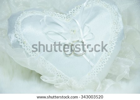 wedding ring on white pillow and soft fabric background, rings and heart is symbols of love and  wedding - stock photo