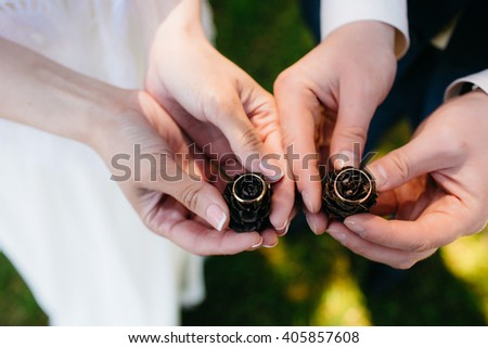 Wedding ring with pine cones in the hands of the bride and groom - stock photo