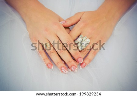 Wedding ring with stones on the hand of the bride on the background of wedding dress