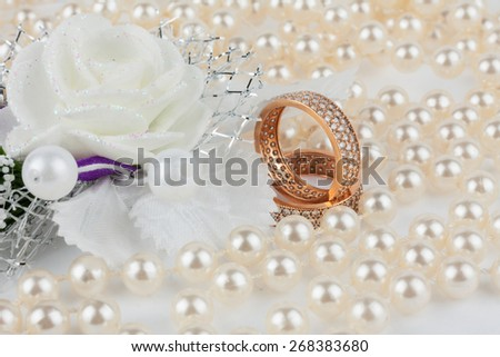 Wedding rings among the pearls with flower, as background - stock photo