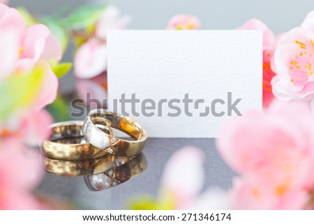 wedding rings and a memo and flowers - stock photo