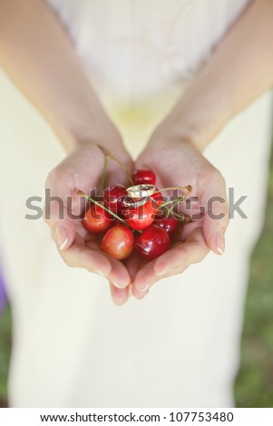 wedding rings and cherry in the hands of the bride - stock photo