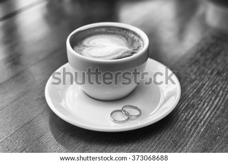 wedding rings and cup of coffee with foam in the form of heart - stock photo